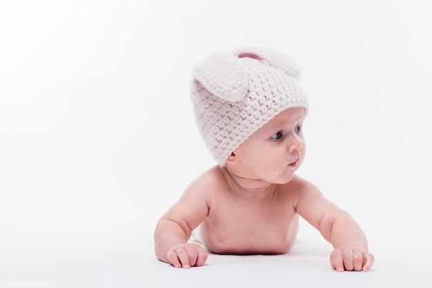 Linda niña acostada desnuda sobre un fondo blanco con un sombrero
