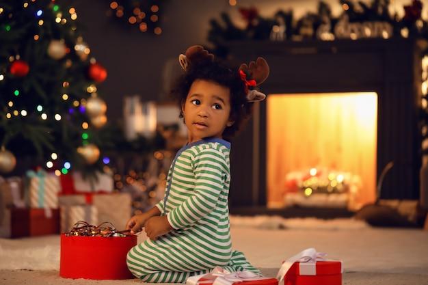 Linda niña afroamericana con regalo en casa en la víspera de navidad