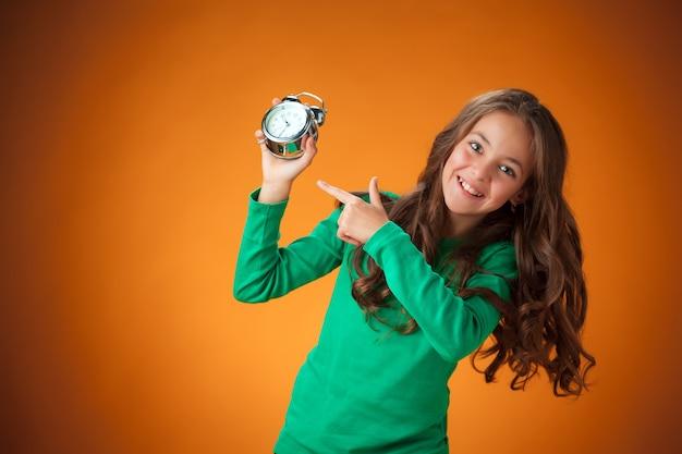 La linda niña alegre en la pared naranja