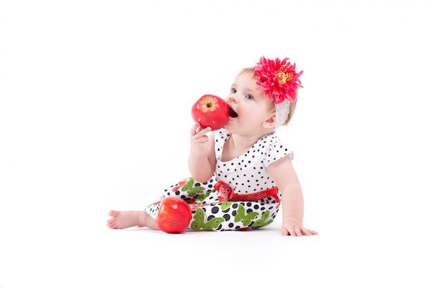 Linda niña alegre en vestido y abrigo comer manzana