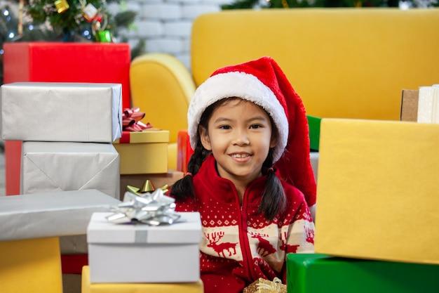 Linda niña asiática con cajas de regalo y decoración para celebrar el festival de navidad