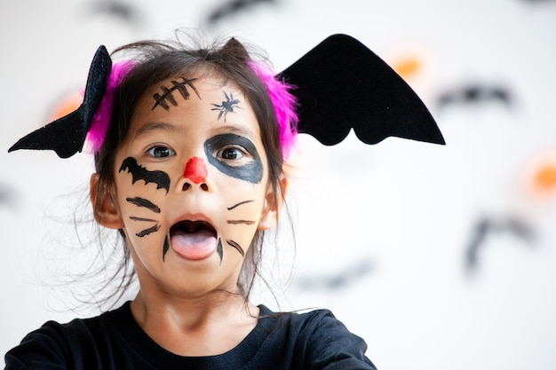Linda niña asiática con disfraces de halloween y maquillaje divirtiéndose en la celebración de halloween