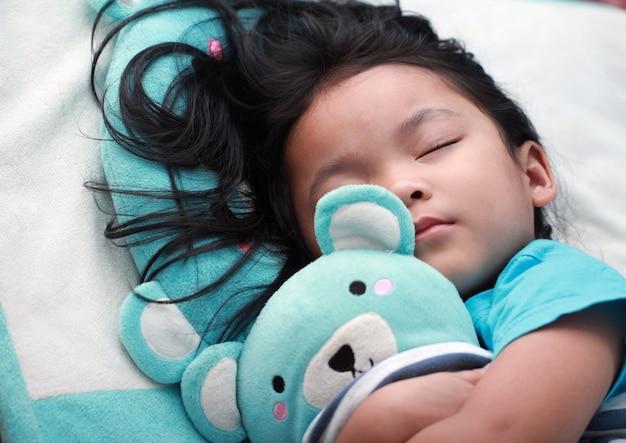 Linda niña asiática dormir y abrazar oso de peluche