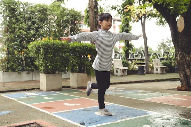 Linda niña asiática jugando a la rayuela al aire libre. divertido juego de actividades para niños en el patio de recreo al aire libre. deporte callejero de verano en el patio trasero para niños. estilo de vida de la infancia feliz.