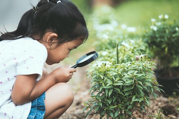 Linda niña asiática niño mirando a través de una lupa en el árbol en el jardín