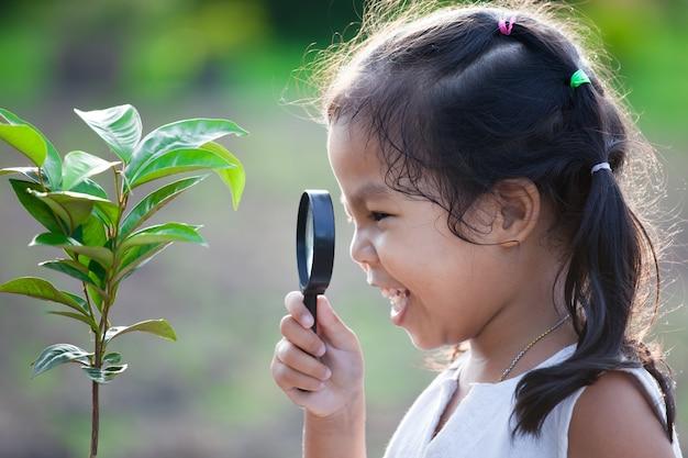 Linda niña asiática niño mirando a través de una lupa en árbol joven en el parque
