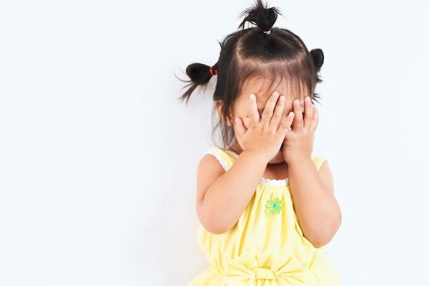 Linda niña asiática que cierra su cara y juega a peekaboo u oculta y busca con diversión