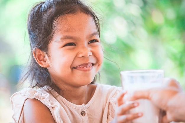 Linda niña asiática que sonríe cuando obtiene un vaso de leche de su madre