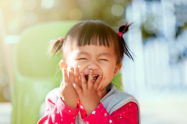 Linda niña asiática riendo y jugando a peekaboo o al escondite con diversión