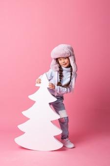 Una linda niña asiática con un sombrero de invierno se encuentra junto a un árbol de navidad sobre un fondo rosa. concepto de invierno, espacio para texto