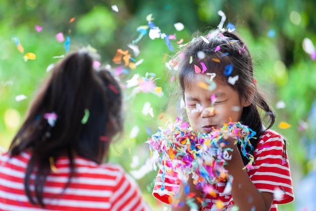 Linda niña asiática y su hermana juegan con confeti de colores juntos para celebrar en la fiesta