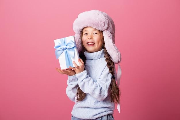 Linda niña asiática con un suéter y gorro de invierno tiene una caja de regalo. concepto de navidad, espacio de texto