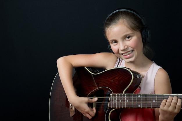 Una linda niña con auriculares tocando la guitarra