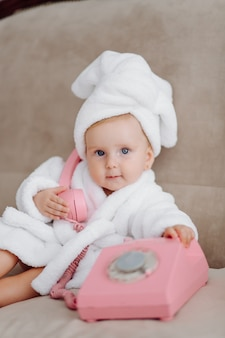 Linda niña en bata de baño blanca