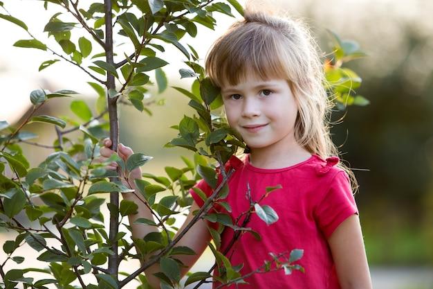 Linda niña bonita con ojos grises y cabello largo y rubio sonriendo tímidamente sosteniendo un árbol joven