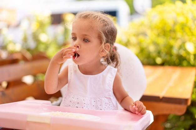 Linda niña caucásica comiendo espaguetis en la mesa sentado en el asiento infantil