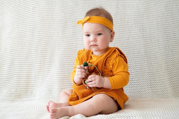 Linda niña caucásica jugando con perlas para la dentición. juguetes para niños pequeños. desarrollo temprano