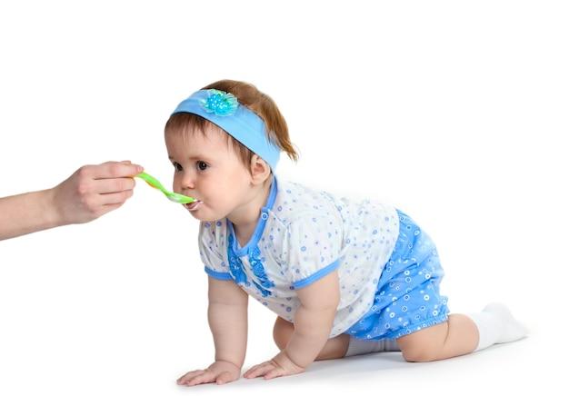 Linda niña comiendo aislado en blanco