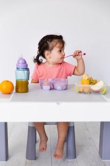 Linda niña comiendo frutas y bebiendo jugo