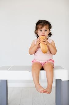 Linda niña comiendo pan