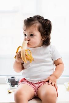 Linda niña comiendo plátano