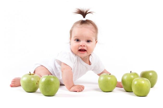 Linda niña confundida en camisa blanca y manzanas