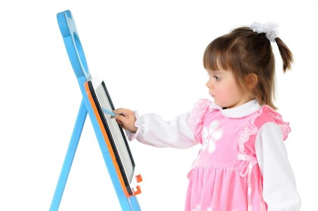 Linda niña dibuja cuidadosamente con tiza en el tablero de los niños. foto de retrato, pared blanca