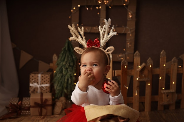Una linda niña con un disfraz de año nuevo saca bolas navideñas de una bolsa de regalos