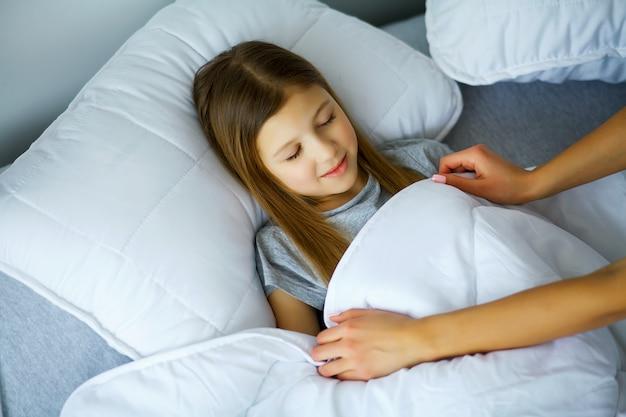 Linda niña duerme en la cama en casa, mamá la cubre con un edredón