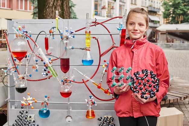 Linda niña en edad escolar posa cerca de un modelo con un proceso químico