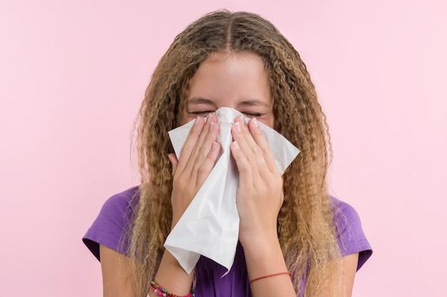 Linda niña estornudando en un pañuelo soplando su nariz que moquea.
