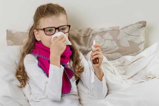 Linda niña estornudando en un pañuelo soplando su nariz que moquea