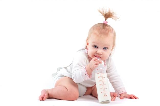 Linda niña feliz en camisa blanca con leche