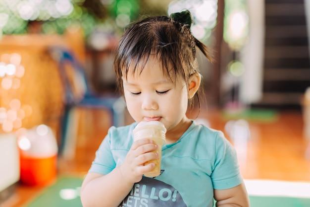 Linda niña feliz está comiendo helado en verano. imagen para el concepto de dulce, gordo y