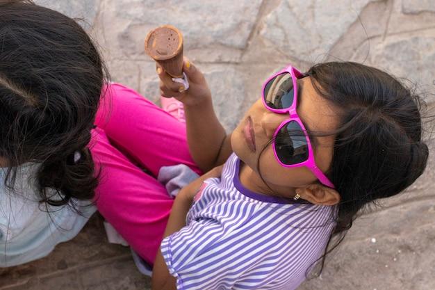 Linda niña con gafas de sol comiendo un delicioso helado