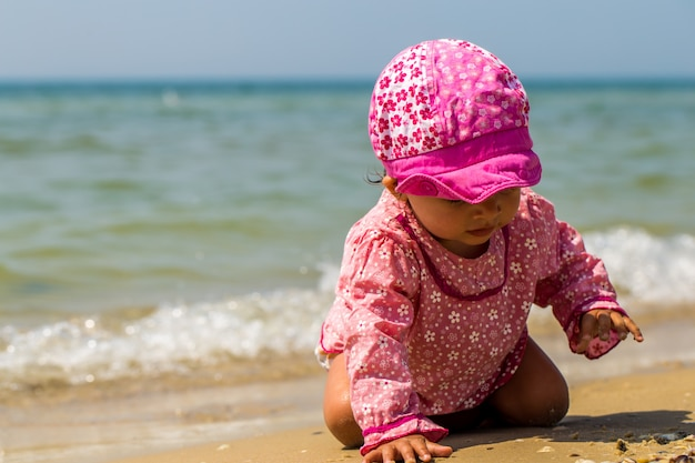 Linda niña gateando en la playa, el niño alegre, emociones