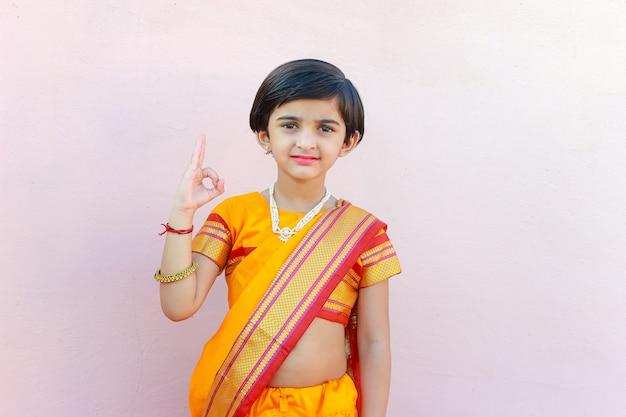 Linda niña india en traje de tradición señalando