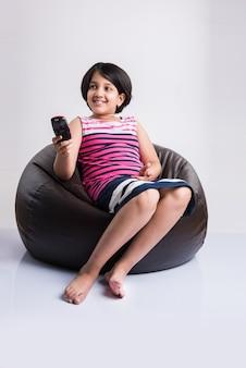Linda niña india viendo la televisión o la televisión mientras cambia de canal con el control remoto, sentado sobre una bolsa de frijoles, aislado sobre fondo blanco.