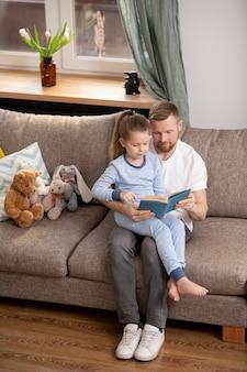 Linda niña inteligente en pijama sentada sobre las rodillas de su padre mientras ambos leen un interesante libro de cuentos en el hogar.