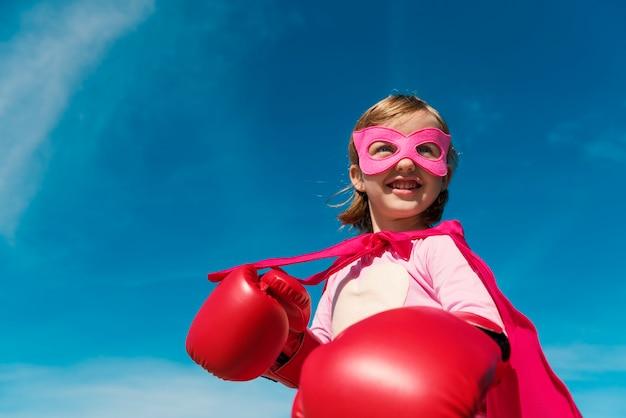 Linda niña jugando superhéroe