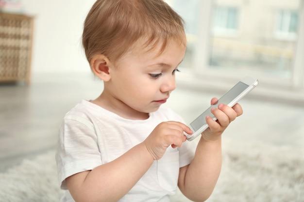 Linda niña jugando con un teléfono inteligente