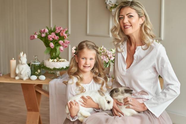 Linda niña y madre jugando con conejo