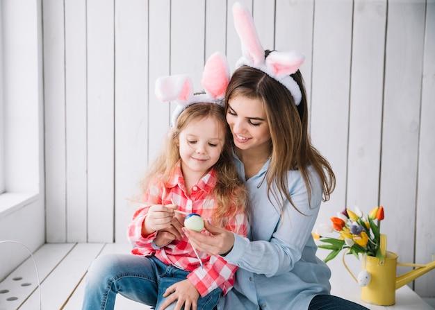 Linda niña y madre en orejas de conejo pintando huevos para pascua