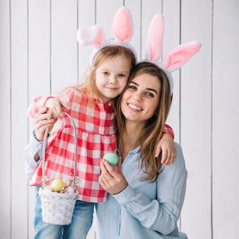 Linda niña y madre de pie con canasta de huevos de pascua