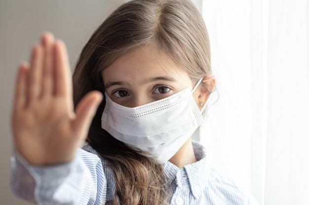 Una linda niña con una máscara protectora desechable del coronavirus. detener el concepto de coronavirus.