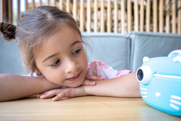 Una linda niña mira la cámara de juguete azul de sus hijos para imprimir fotos al instante.