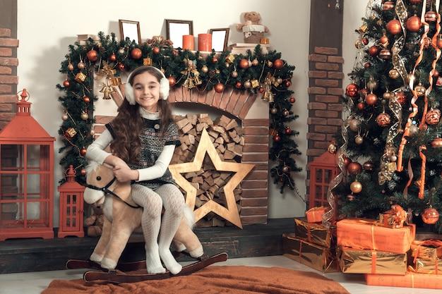 Linda niña morena con el pelo largo sentado en un caballo de juguete en navidad decorado habitación.