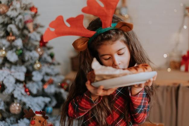 Linda niña morena en pijama rojo con cuernos de ciervo en la cabeza está comiendo un pastel de navidad