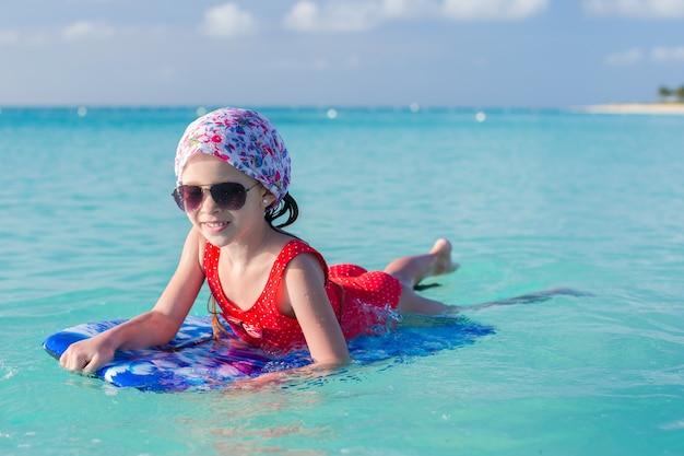 Linda niña nadando en una tabla de surf en el mar turquesa