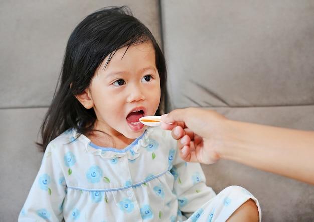 Linda niña niño recibiendo píldora en casa
